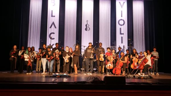 National act Black Violin on stage with local students